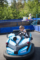 Little girl rides on toy electric cars blue in the Park