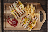 Top view of chicken club sandwiches and french fries on rustic wooden table