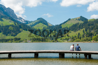 Schwarzsee, FR / Switzerland - 1 June 2019: two men best friends enjoy the summer lakeside view at the Schwarzsee Lake in the Swiss Alps in canton Fribourg