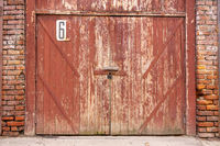 Old garage door in a white concrete wall. Gates made of wood painted with cracked green paint