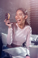 Beautiful smiling girl holding donut and relaxing on her bed at home