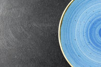close up of blue ceramic plate on slate background
