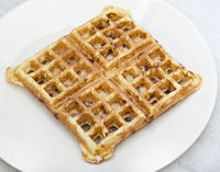 Homemade square belgian waffle on white plate