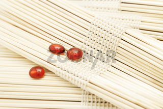 Red Glass Pebbles On Blurred Wooden Sets. Spa Wellness Concept