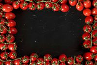 Group of cherry tomatoes on black marble like board, arranged in frame around, rectangular space for text in middle