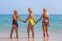 Three blond girls stand in sea water