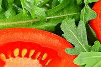 Closeup detail on bright red tomato slice and wet green arugula rocket leaves salad