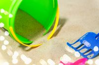 close up of bucket and rake on beach sand