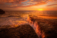 Tidal waterfalls coloured by summer sunrise scenic landscape Australia