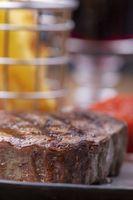 Nahaufnahme vom gegrilltes Steak mit Pommes frites
