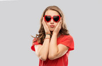 girl in red heart shaped sunglasses pouting