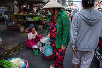 Elderly Asian woman in bright outfit with Chinese hat shopping for vegetables at a street market.