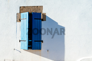 Old window with wooden blue painted shutters
