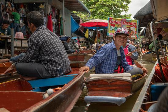 Boy in boat smiles in floating market