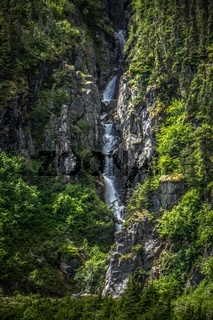 small waterfalls on mountain slopes in alaska mountains