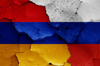 flags of Armenia and Russia painted on cracked wall