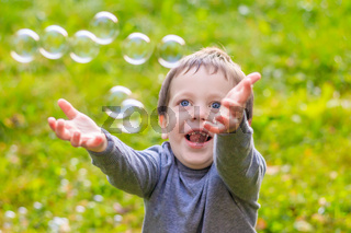 A boy on the street catches soap bubbles. Happy childhood. Children's games.