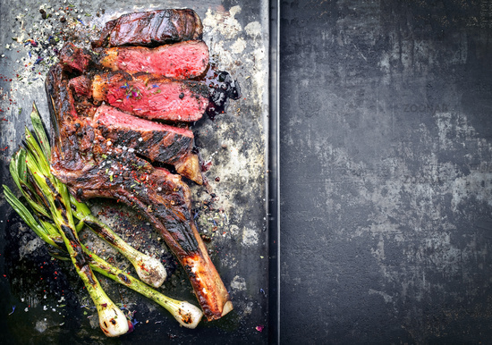 Barbecue dry aged wagyu tomahawk steak with leek as top view on a black metal sheet with copy space