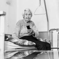 Elderly 96 years old woman operating TV or DVD with remote control in black and white.