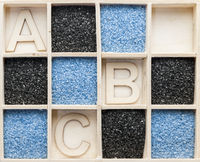 Wooden box with sand and A B C letters