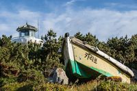 Ganjeolgot Lighthouse with broken boat in front inside nature near coastline. Easternmost Point of Peninsula in Ulsan, South Korea. Asia
