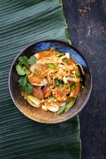 Traditional Thai kaeng phet red curry with clams and vegetable as top view in a bowl with copy space right