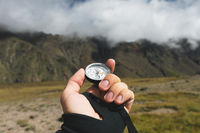 Viewpoint shot. A first-person view of a man's hand holds a compass against the background of an epic landscape with cliffs hills and a blue sky with clouds