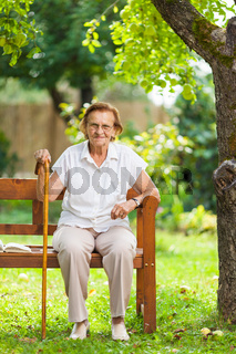Elderly woman sitting and relaxing on a bench outdoors in park