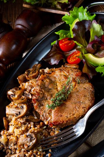 Pork steak with mushrooms and buckwheat groats and mango salad