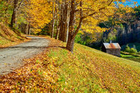 Dirt unpaved road at autumn in Vermont, USA.