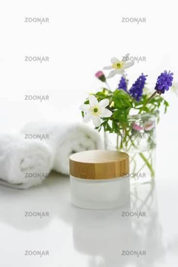 White towels next to a cream jar in front of white background and flowers in a vase.