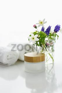 Weiße Handtücher neben einer Cremedose vor weißem Hintergrund und Blumen in einer Vase.