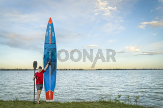 male paddler and paddleboard on lake shore