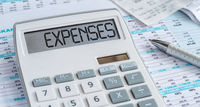 A calculator with the word Expenses on the display