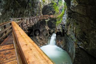 Hiking along a woodend boardwalk in a canyon near Kaprun, Austria
