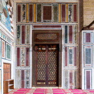 Old colorful marble wall with wooden door decorated with arabesque ornaments, Cairo, Egypt