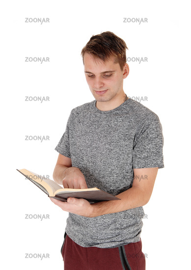 Young man standing reading his book
