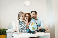 Going on adventure, mom, dad and daughter studying globe.