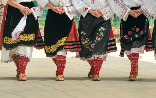 Girls dancing folk dance. People in traditional costumes dance Bulgarian folk dances. Close-up of fe