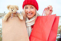 Winter woman holding retail shopping or gift bags