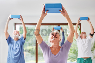Senioren machen Rückentraining mit Yogablock