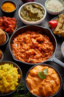 Various Indian dishes on a table. Spicy chicken Tikka Masala in iron pan