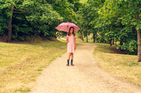 Girl with umbrella walking in a park