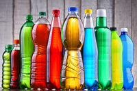 Plastic bottles of assorted carbonated soft drinks in variety of colors.