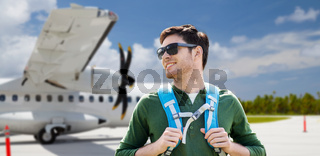 smiling man with backpack over plane on airfield