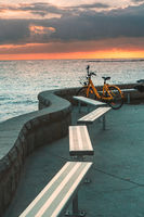 Bicycle and empty bench seats overlooking ocean at sunrise