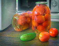 Canned ripe tomatoes in large glass jars.