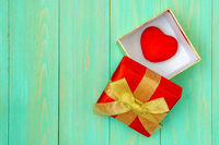Red heart in gift box on wooden plank