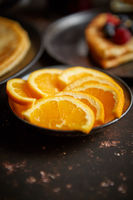 Close up on fresh orange slices placed on ceramic saucer