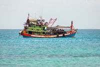 Traditional large scale industrial fishing boat with crew on deck in calm tropical waters.